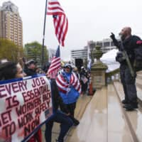 Protesters demonstrate against Michigan's lockdown at the state capitol in Lansing on Thursday. More than 1.26 million state residents have filed for unemployment benefits since March 15. | LANSING STATE JOURNAL / VIA AP