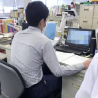 A worker receives a call at a public health center in Fujisawa, Kanagawa Prefecture, earlier this month. The computer screen is blurred for privacy reasons. | KYODO