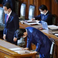 Prime Minister Shinzo Abe (right) bows at the Upper House plenary session Thursday after the fiscal 2020 supplementary budget was approved. | KYODO