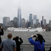 Spectators on the New Jersey shoreline take pictures as the U.S. Navy hospital ship USNS Comfort departs Manhattan on Thursday as it sails back to its home port of Norfolk, Virginia, after treating New York City area coronavirus patients. | REUTERS
