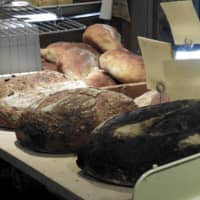 Fresh from the oven: Loaves of olive sourdough (right), Hokkaido wheat (center) and campagne (French sourdough) sit cooling on blocks in Lee's Bread.    JOAN BAILEY