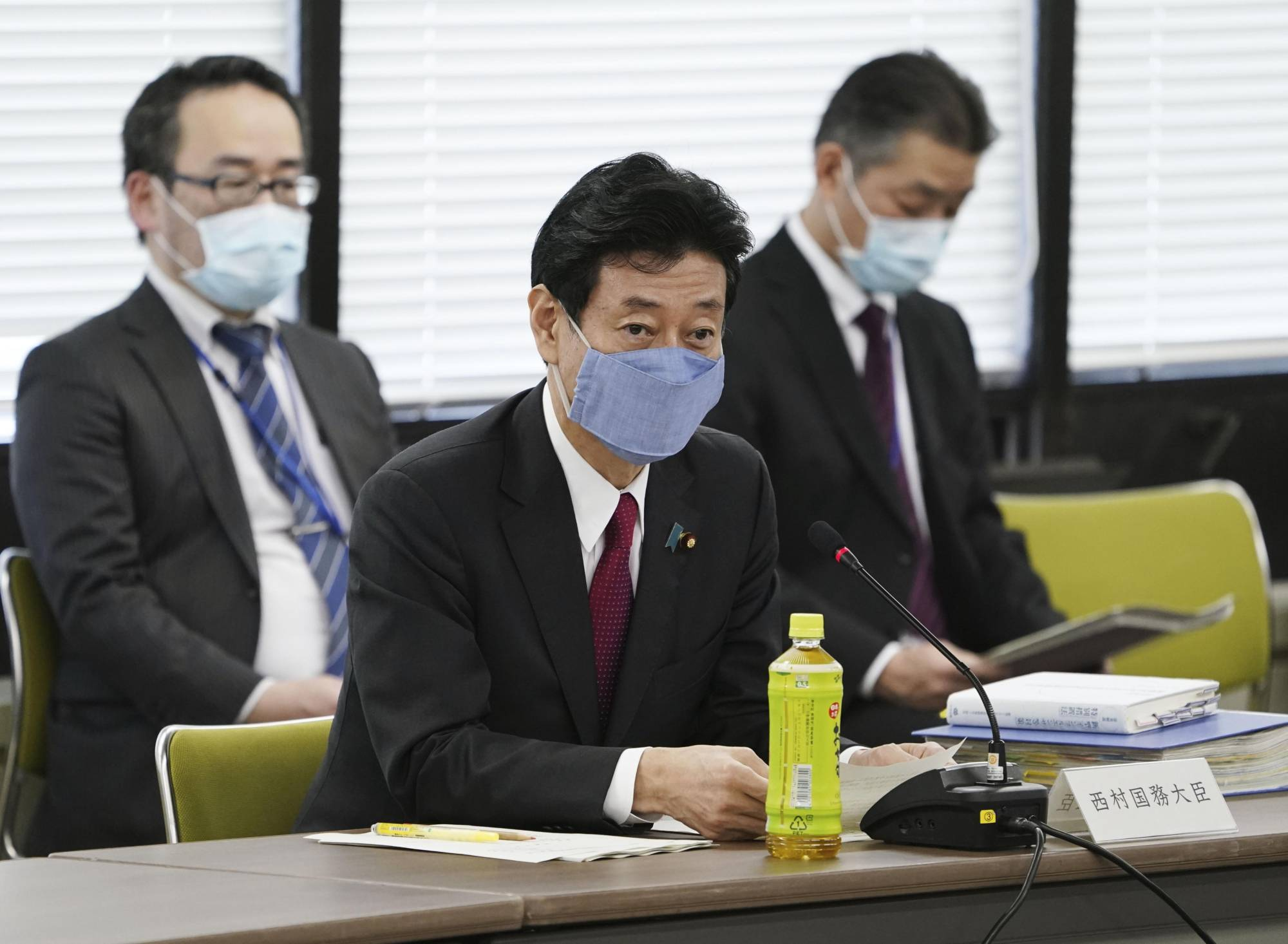 Economic revitalization minister Yasutoshi Nishimura (front) speaks at a meeting of a government panel of experts working on measures against the new coronavirus on Friday in Tokyo. | KYODO