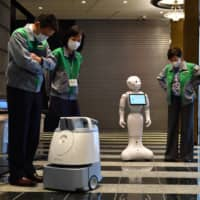 Tokyo Gov. Yuriko Koike (right) on Friday visits a hotel in Tokyo's Sumida Ward that uses robots for serving and greeting COVID-19 sufferers. | YOSHIAKI MIURA