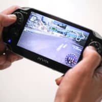 A man plays the game Ridgeracer on a Sony Corp.PlayStation Vita games console in London. | BLOOMBERG