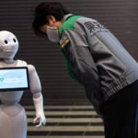 Tokyo Gov. Yuriko Koike greets the robot Pepper on Friday as she visits a hotel that is being used as a medical lodging facility to accommodate COVID-19 coronavirus patients with mild symptoms. | AFP-JIJI