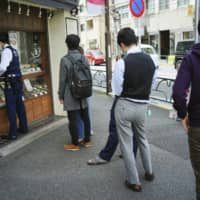 People line up to buy lunch at a shop in Tokyo on April 22. Under Japan's coronavirus state of emergency, people have been asked to stay home but many still have to commute to work. | AP