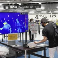 A flight passenger gets a body temperature check-up before boarding at Narita International Airport in Chiba Prefecture, east of Tokyo, on Friday. | KYODO
