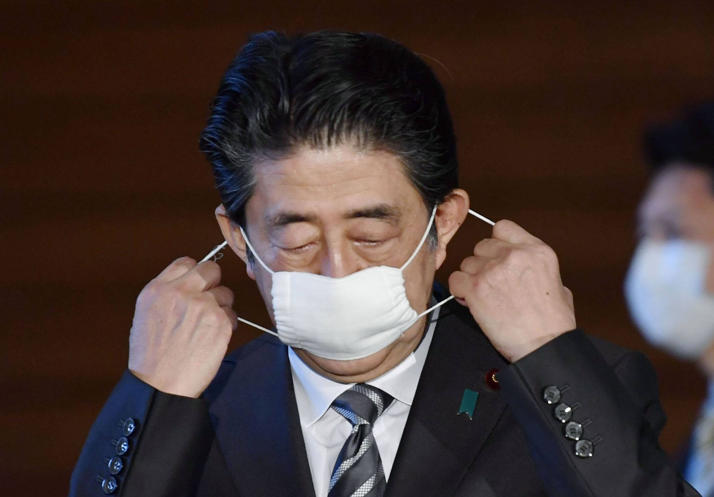 Prime Minister Shinzo Abe takes off his mask during a news conference Friday at his office. | KYODO