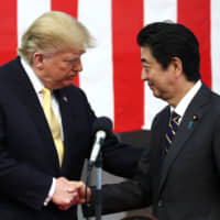 U.S. President Donald Trump shakes hands with Prime Minister Shinzo Abe during a speech to Japanese and U.S. troops aboard the Maritime Self-Defense Force's Kaga helicopter carrier at the Yokosuka naval base in Kanagawa Prefecture in May last year. | POOL / VIA REUTERS