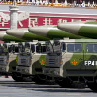 Chinese military vehicles carrying DF-26 intermediate-range ballistic missiles travel past Tiananmen Gate during a military parade to commemorate the 70th anniversary of the end of World War II in Beijing in September 2015. | REUTERS