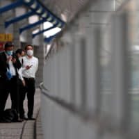 Businessmen wearing protective face masks wait on a pedestrian bridge in a business district of Tokyo on Wednesday. | REUTERS