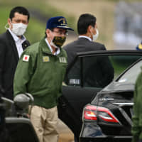 Defense Minister Taro Kono wears a protective face mask while attending a Ground Self-Defense Force live-fire exercise at the East Fuji Maneuver Area in Gotemba, Shizuoka Prefecture, on May 23. | POOL / VIA BLOOMBERG