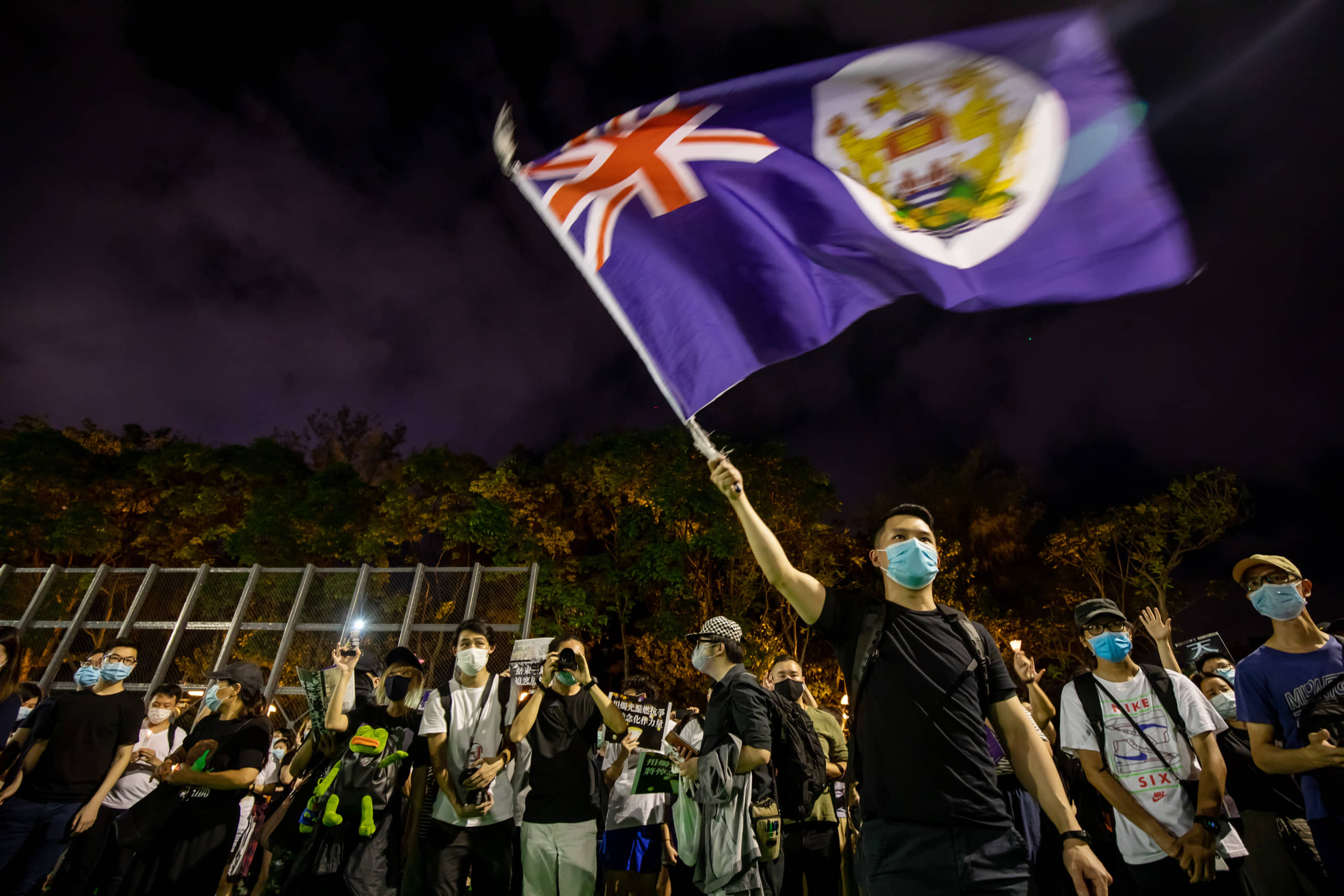 A person wearing a protective face mask waves a colonial-era Hong Kong flag at Victoria Park to commemorate the 31st anniversary of the Tiananmen Square crackdown, in Hong Kong on Thursday. | BLOOMBERG