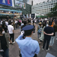 A police officer stands near people gathering to protest during a solidarity rally Saturday in Tokyo's Shibuya Ward over the death of George Floyd in Minneapolis police custody last month. | AP