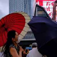A woman wearing a facemask walks with an umbrella in Shibuya on June 11. | AFP-JIJI