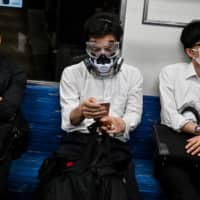 A man wearing a respirator and googles sits on a train in Tokyo on June 25. | AFP-JIJI