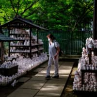 A visitor wearing a face mask walks past maneki statues, also known as beckoning cat, at Gotokuji temple in Tokyo on June 10. | AFP-JIJI