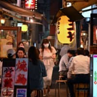 People drink and eat in an alley of izakaya in Tokyo's Shimbashi area on June 17. | AFP-JIJI