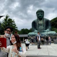 A couple wearing face masks take a selfie with the Great Buddha statue at Kotoku-in temple in Kamakura, Kanagawa Prefecture on Saturday. | AFP-JIJI