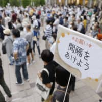 People practice social distancing while listening to a stump speech during an event for the Tokyo gubernatorial election Saturday in the capital. The sign reads: 'Let's keep our distance.'  | KYODO