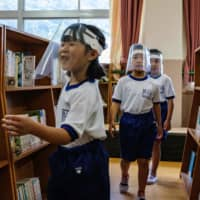 Students wearing face shields visit the library in Kinugawa Elementary School in Nikko, Tochigi Prefecture, on Friday. | AFP-JIJI