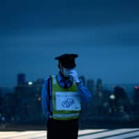 A security guard wearing a facemask and a vest with a notice of 'Please do not touch' stands guard at the Shibuya Sky observation deck in Tokyo on June 24. | AFP-JIJI