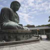 A woman wearing a face mask to protect against the spread of the new coronavirus visits the Great Buddha statue at Kotoku-in Temple in Kamakura, Kanagawa Prefecture, on Tuesday. | AP