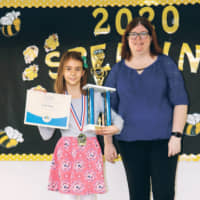 Katie Petty holds a trophy and a certificate after the Yokota West Elementary School bee. | YOKOTA WEST ELEMENTARY SCHOOL