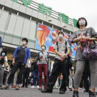 Passersby listen to a Tokyo gubernatorial candidate's speech outside Shinjuku Station on Thursday.  | KYODO