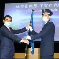 Defense Minister Taro Kono hands the unit flag of the Space Operations Squadron to the head of the unit, Toshihide Ashiki, on May 18. | KYODO