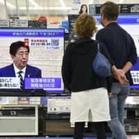 Prime Minister Shinzo Abe's news conference is aired on TVs at an electronics store in Urayasu, Chiba Prefecture last week.  | KYODO