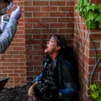 A medic protester assists a member of the media after police started firing tear gas and rubber bullets near the 5th police precinct during a demonstration to call for justice for George Floyd on Saturday in Minneapolis. | AFP-JIJI