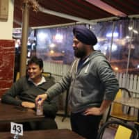 Gurmeet Tuli, who owns a jewelry shop, speaks with fellow small business owners at an Indian restaurant in the Parramatta suburb of western Sydney. | REUTERS