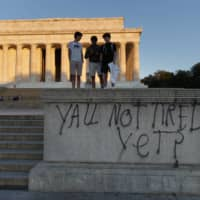 Spray paint that reads 'Yall Not Tired Yet?' is seen on the base of the Lincoln Memorial on the National Mall in Washington, early Sunday. | AP