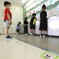Children wait apart from one another as they take turns washing hands at an elementary school in Sapporo on Monday. | POOL / VIA KYODO