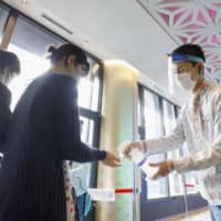 Visitors disinfect their hands at Tokyo Skytree on Monday, as the tower reopens after being closed due to the coronavirus pandemic. | KYODO