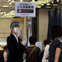 An employee wearing a face shield holds up a sign as people wait in a queue to visit a Matsuzakaya department store in Tokyo as it reopened for business on May 26. | AFP-JIJI