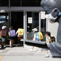 Children walk into a school in Sapporo on Monday as the facility resumed a week after Prime Minister Shinzo Abe announced an end to the coronavirus state of emergency in Hokkaido Prefecture. | KYODO