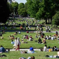 People relax in Paris' Jardin de Montsouris park on Sunday, the second day of reopening following the nationwide lockdown put into place on March 17 to in response to the coronavirus outbreak. | AFP-JIJI