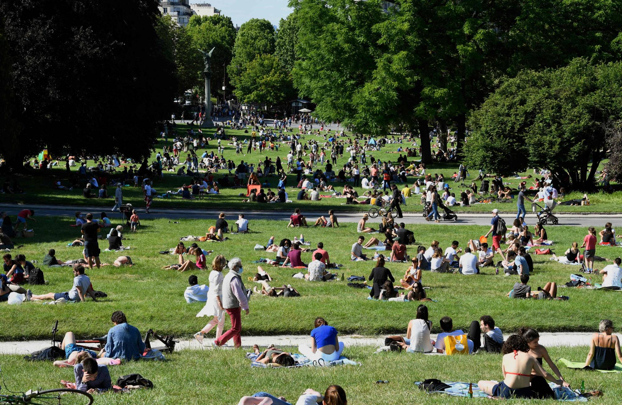 People relax in Paris' Jardin de Montsouris park on Sunday, the second day of reopening following the nationwide lockdown put into place on March 17 to in response to the coronavirus outbreak.   AFP-JIJI