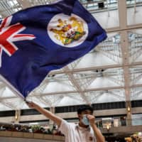 A pro-democracy protester waves a British colonial flag during a rally at a shopping mall in the Central district in Hong Kong on Monday. | AFP-JIJI