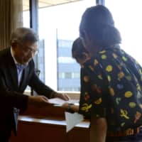 An LGBT couple receives a certificate recognizing their partnership from the deputy mayor of Kumamoto last August. | KYODO