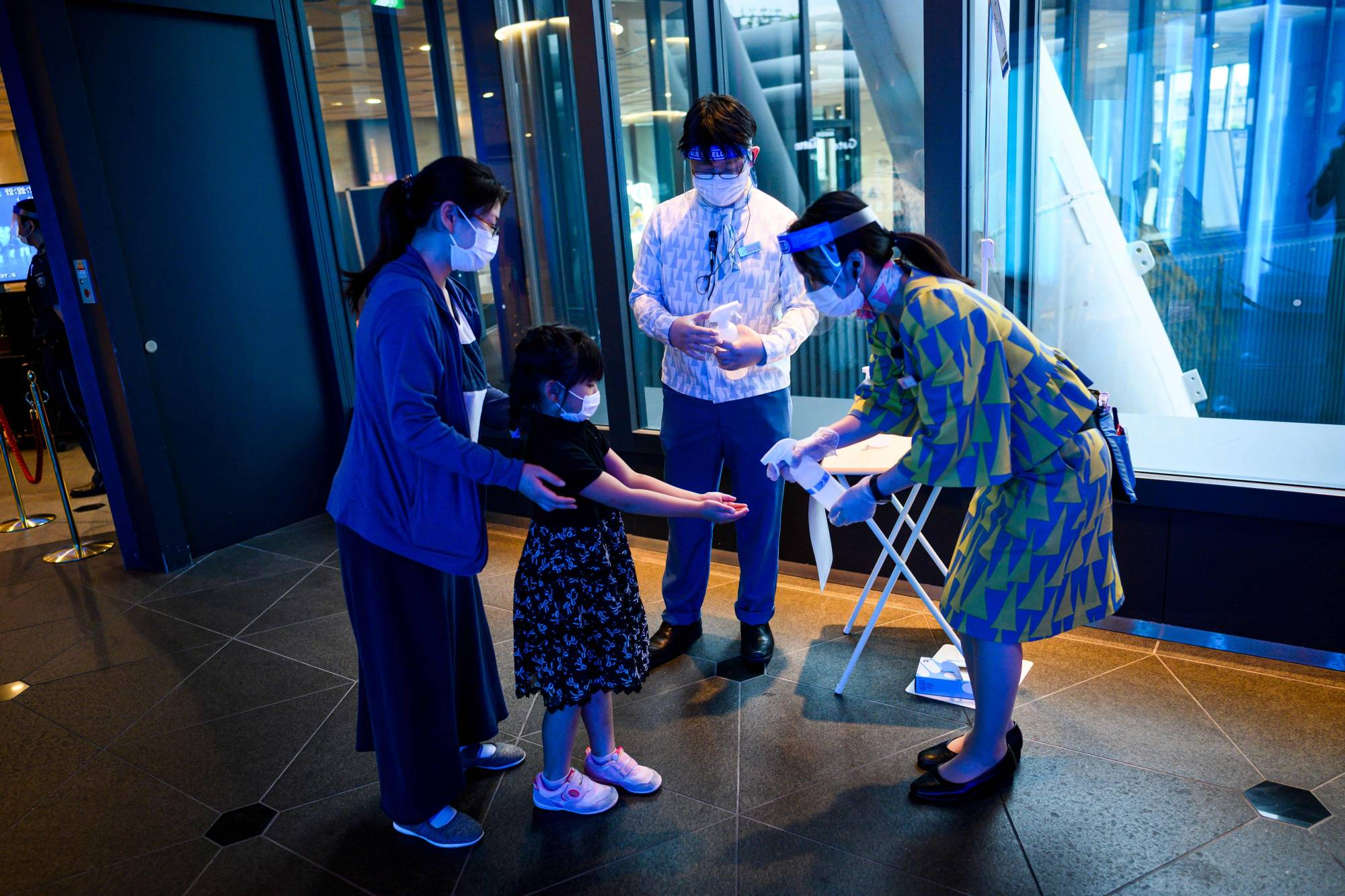 Employees spray hand sanitizer for visitors at Tokyo Skytree on Monday as the city's landmark reopened a week after the lifting of a state of emergency. | AFP-JIJI