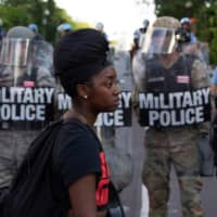 A demonstrator walks in front of a row of military police members wearing riot gear outside the White House on Monday. | AFP-JIJI