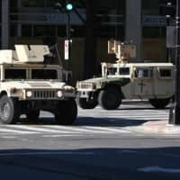 Military vehicles take up positions on the streets of Washington on Monday. | AFP-JIJI