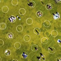 People in San Francisco's Dolores Park sit inside painted circles designed to help them keep a healthy distance to prevent the spread of the coronavirus.  | AP