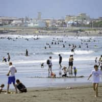 People enjoy themselves on a beach in Fujisawa, Kanagawa Prefecture, on May 24, a day before the state of emergency was lifted for the entire nation. | KYODO