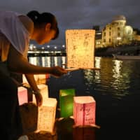 A girl releases paper lanterns on the Motoyasu River facing the gutted Atomic Bomb Dome in remembrance of atomic bomb victims on the 74th anniversary of the bombing of Hiroshima on Aug. 6 last year. | KYODO