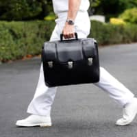 A military aide carries a briefcase containing launch codes for nuclear weapons as U.S. President Donald Trump returns to the White House in Washington in July 2018. | REUTERS