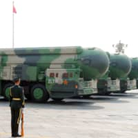 Military vehicles carrying DF-41 intercontinental ballistic missiles travel past Beijing's Tiananmen Square during a military parade marking the 70th founding anniversary of the People's Republic of China on October 1 last year. | REUTERS